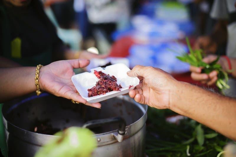 As mãos dos refugiados foram ajudadas pelo alimento da caridade para aliviar a fome: Conceitos de alimentação: A mão ofereceu doa foto de stock