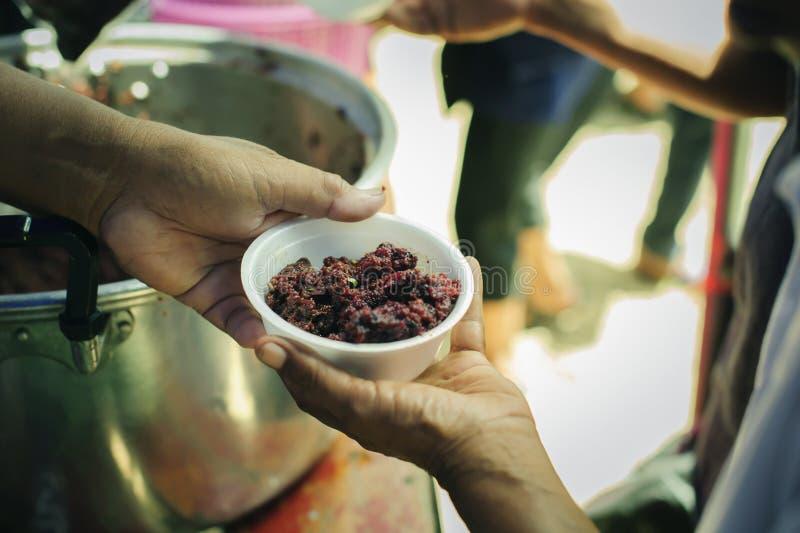 As mãos dos refugiados foram ajudadas pelo alimento da caridade para aliviar a fome: Conceitos de alimentação: A mão ofereceu doa fotos de stock