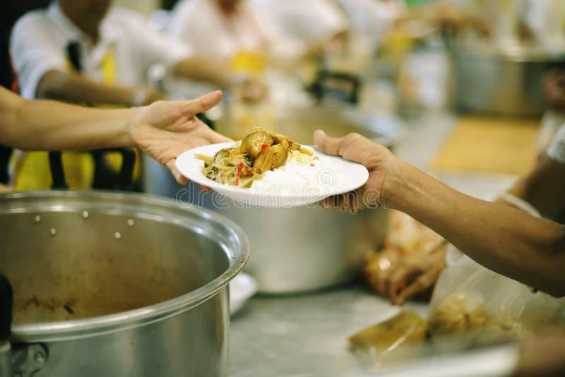 As mãos dos refugiados foram ajudadas pelo alimento da caridade para aliviar a fome: o conceito do humanitarismo fotografia de stock