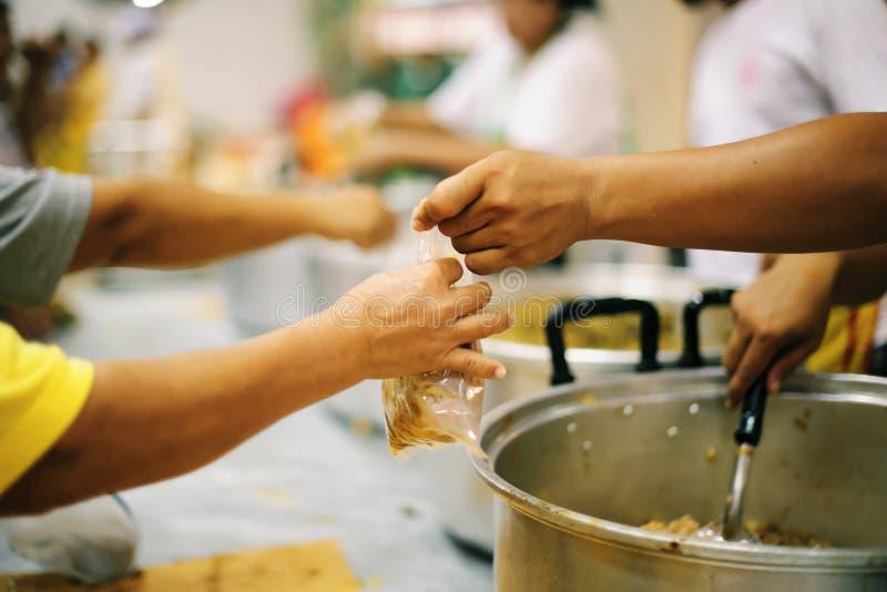 As mãos dos refugiados recebem o alimento cômico da caridade: O conceito da falta de alimentos foto de stock royalty free