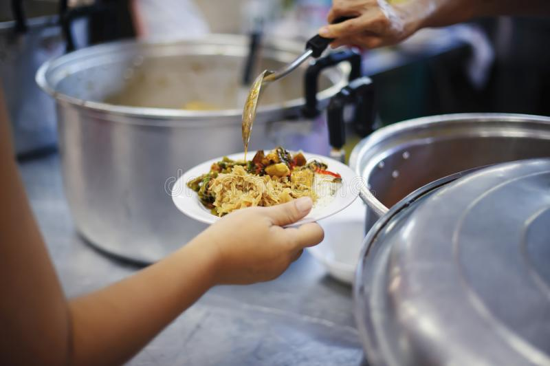 As mãos dos refugiados recebem o alimento cômico da caridade: O conceito da falta de alimentos imagem de stock