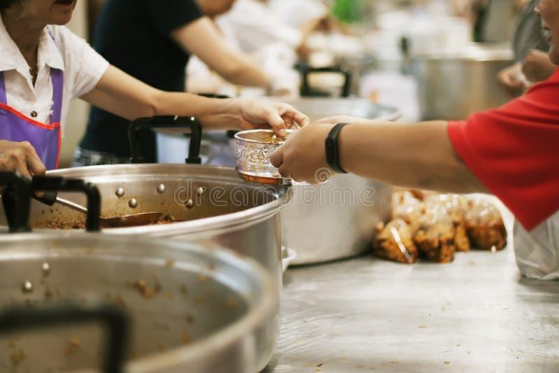 As mãos dos refugiados recebem o alimento cômico da caridade: O conceito da falta de alimentos fotos de stock
