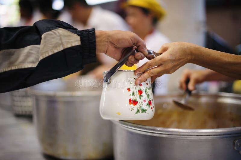 As mãos dos refugiados recebem o alimento cômico da caridade: O conceito da falta de alimentos imagem de stock royalty free