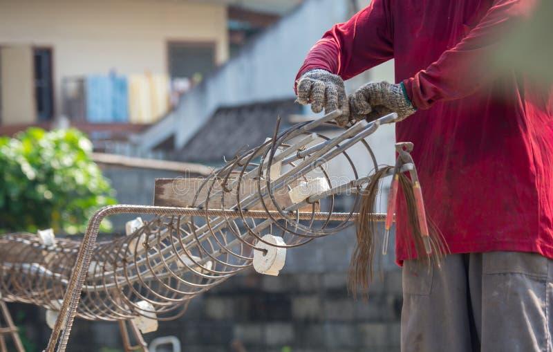 As mãos dos trabalhadores calçaram luvas usando a mão para passar o fio para amarrar para a estrutura a casa ou a construção fotos de stock