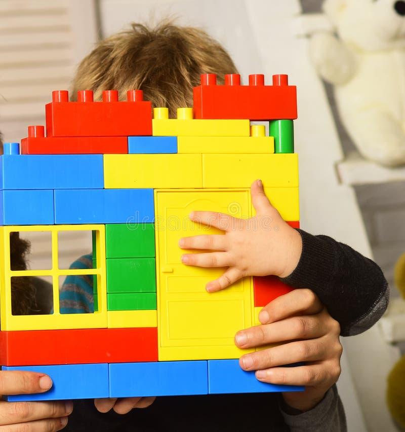 As mãos e a criança masculinas guardam a construção de tijolos colorida do brinquedo imagem de stock royalty free