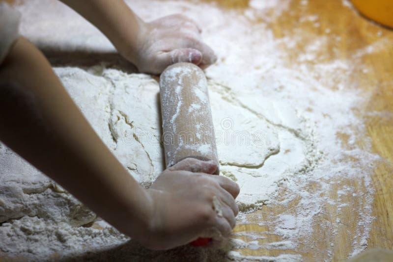 As mãos e a massa das crianças Rapaz pequeno que amassa uma massa Conceito feito a mão saudável do alimento produtos da padaria,  fotografia de stock royalty free