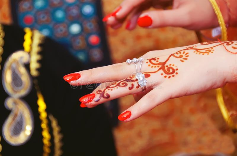 As mãos e os dedos são tirados à hena Mão fêmea com tatuagem da hena Foco seletivo macio, fim acima Há laca vermelha e imagens de stock royalty free