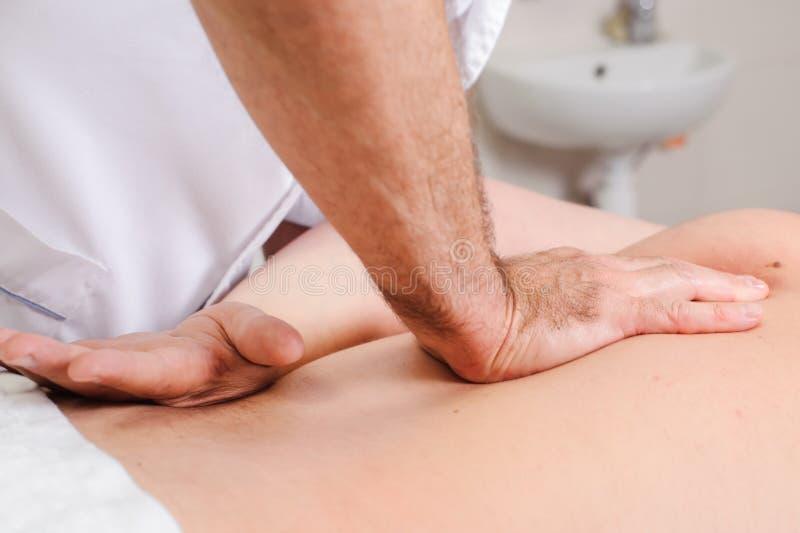 As mãos e um cliente do massagista para trás Paciente recebendo uma massagem traseira no centro dos termas pelo terapeuta profi foto de stock royalty free