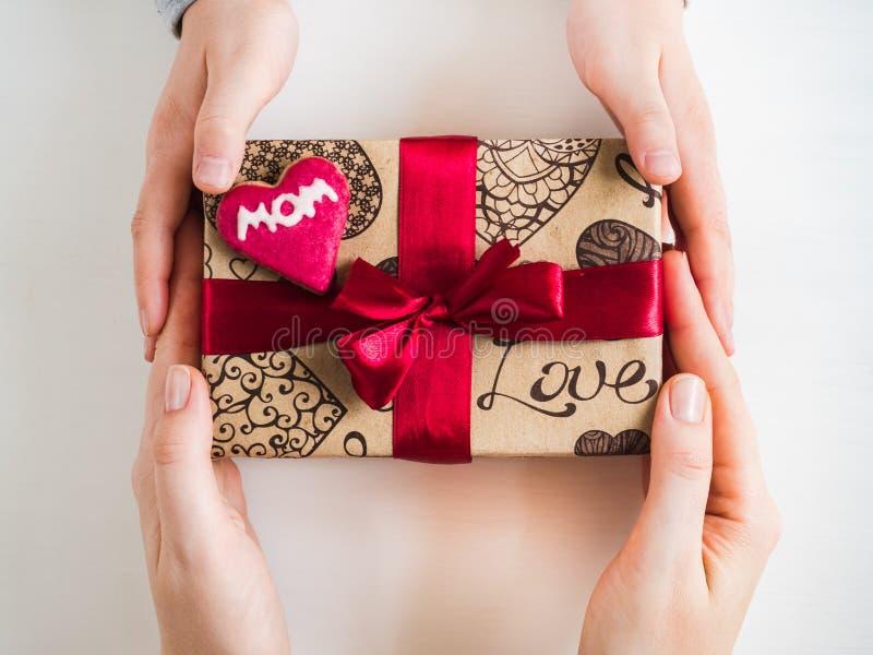 As mãos e uma caixa das crianças com um presente imagem de stock royalty free