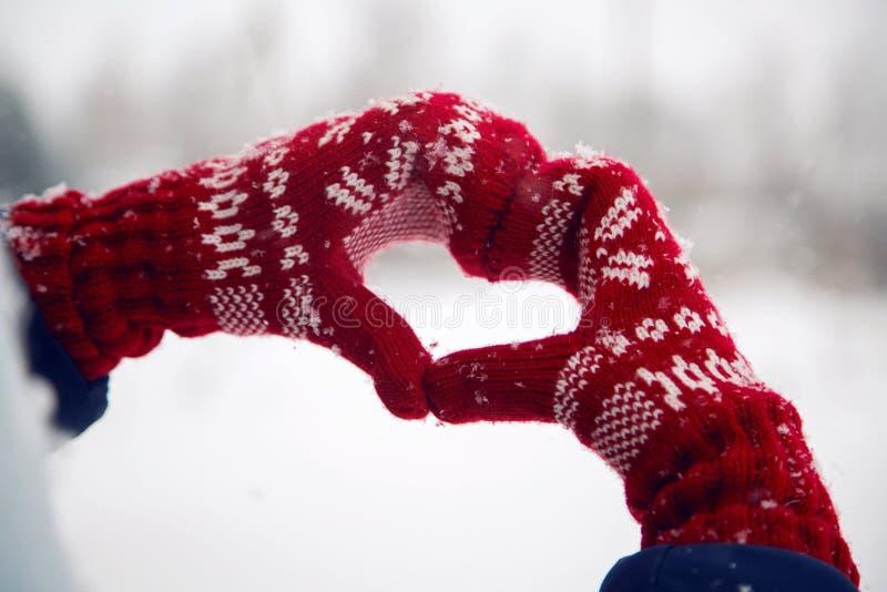 As mãos em mitenes vermelhos dobraram o coração imagens de stock royalty free