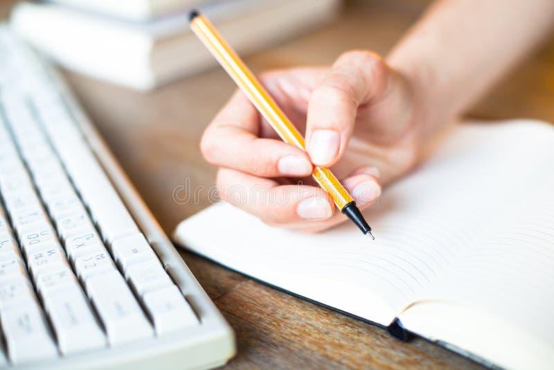 As mãos escrevem uma pena em um caderno. fotos de stock