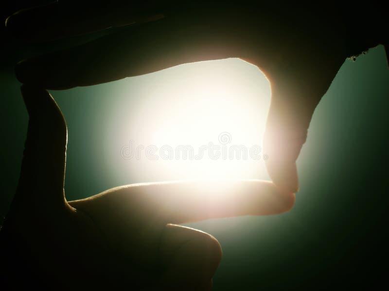As mãos esticam para o sol no nível do lago imagens de stock