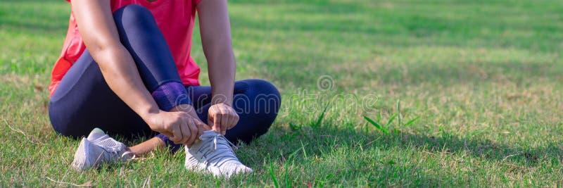As mãos fêmeas ajustam seus tênis de corrida antes da prática Corredor que prepara-se para treinar Conceito ativo do estilo de vi imagens de stock