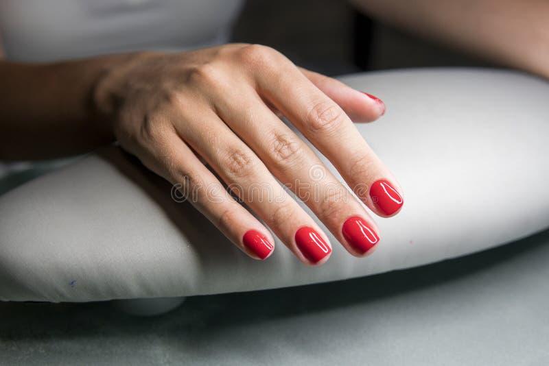 As mãos fêmeas bonitas com os pregos vermelhos na beleza pregam o salão de beleza Pregos e tratamento de mãos fêmeas bonitos fotos de stock