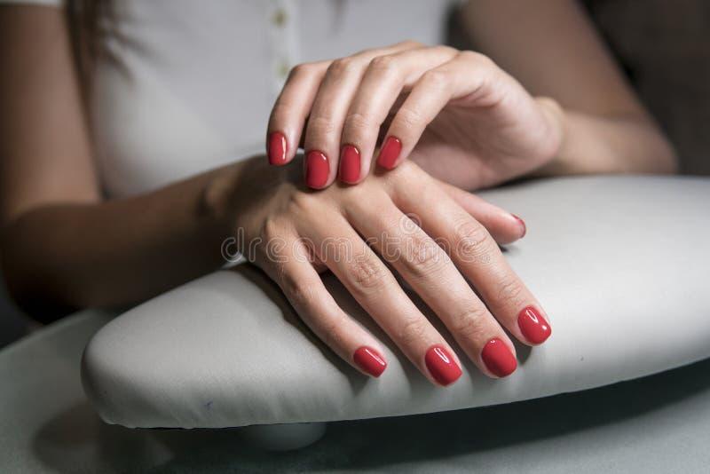 As mãos fêmeas bonitas com os pregos vermelhos na beleza pregam o salão de beleza Pregos e tratamento de mãos fêmeas bonitos foto de stock royalty free