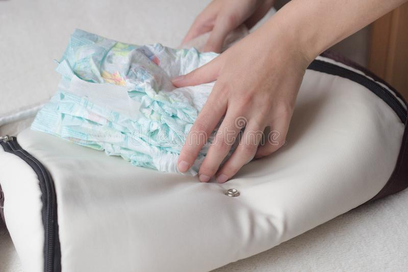 As mãos fêmeas colocam tecidos do bebê em um saco, fim-UPS, tecido fotos de stock