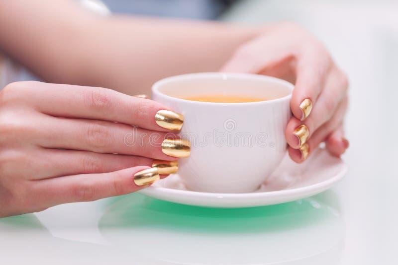 As mãos fêmeas com tratamento de mãos elegante do ouro guardam um copo do chá fotografia de stock