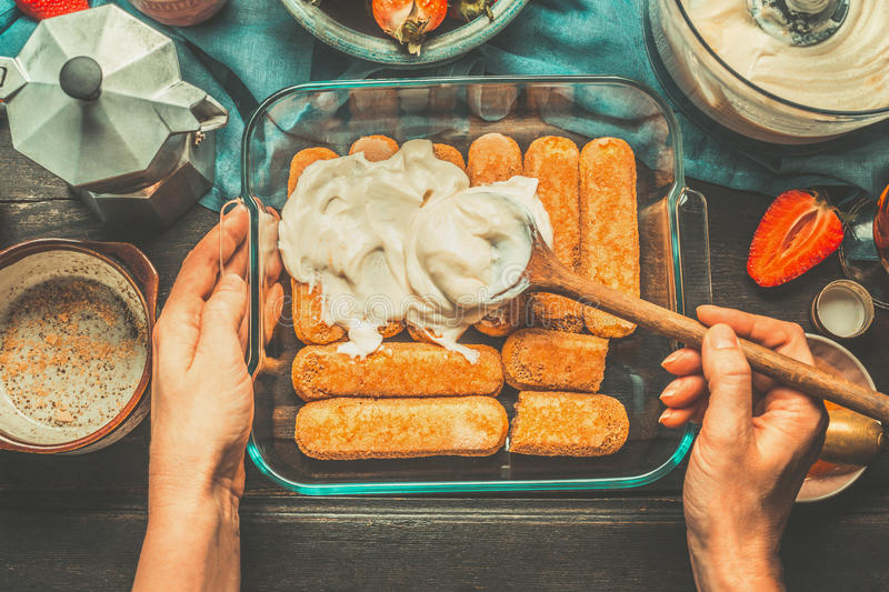 As mãos fêmeas da mulher mancharam o creme no bolo no fundo de madeira rústico escuro, vista superior Conceito italiano do alimen foto de stock