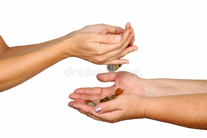 As mãos fêmeas derramam abaixo das moedas em uma outra pessoa fotos de stock royalty free