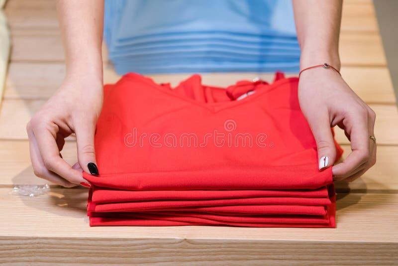 As mãos fêmeas dobram camisas vermelhas, loja de roupa imagens de stock royalty free