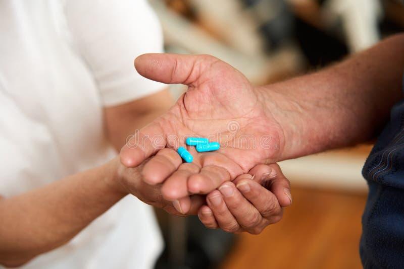 As mãos fêmeas e masculinas velhas com comprimidos foto de stock
