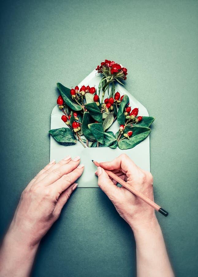 As mãos fêmeas escrevem com o cartão do lápis no aberto envolvem com arranjo vermelho das bagas e de flores da decoração do outon fotos de stock