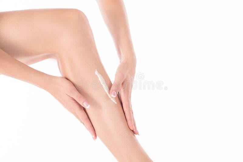 As mãos fêmeas fazem massagens o pé da mulher com loção do corpo, fim acima imagem de stock royalty free