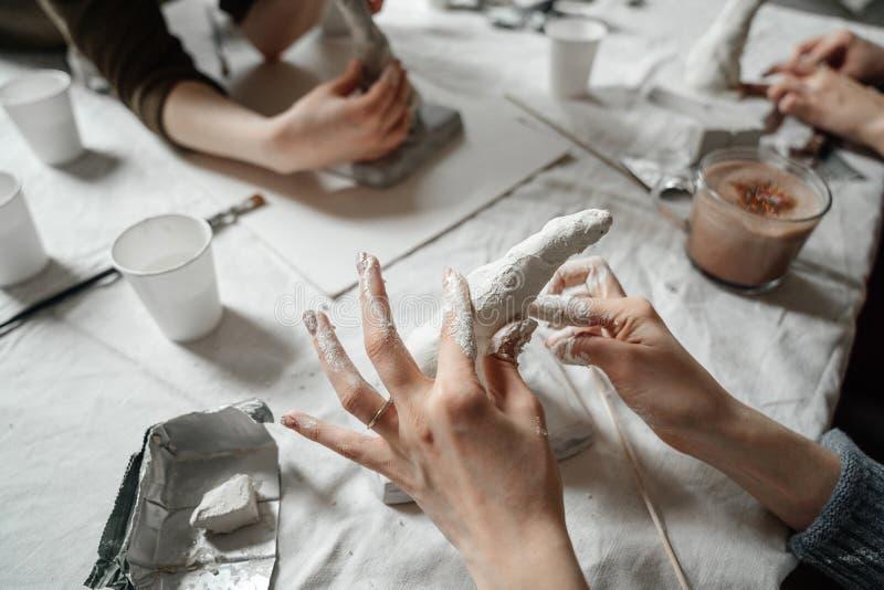 As mãos fêmeas fazem moldes do plástico e do emplastro na classe Oficina e trabalho criativo da equipe na produção fotografia de stock royalty free