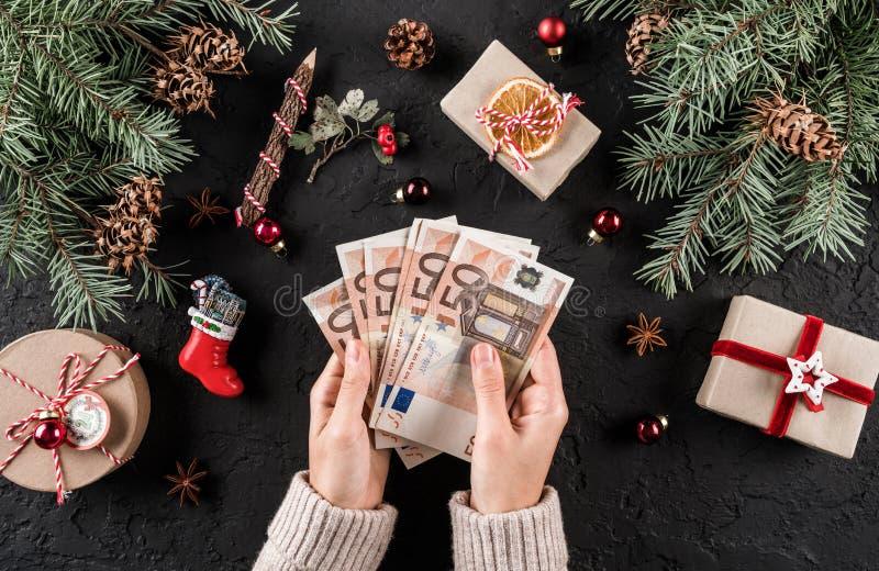 As mãos fêmeas guardam o dinheiro para comprar no fundo do Natal com ramos do abeto, cones do pinho, presentes Tema do Xmas e do  fotografia de stock royalty free