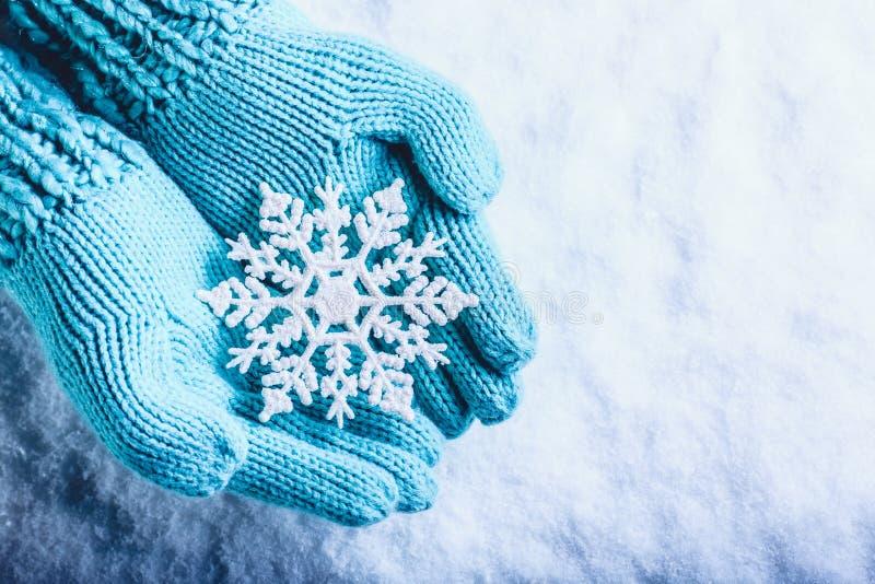 As mãos fêmeas na cerceta clara fizeram malha mitenes com o floco de neve maravilhoso efervescente em um fundo branco da neve Con foto de stock
