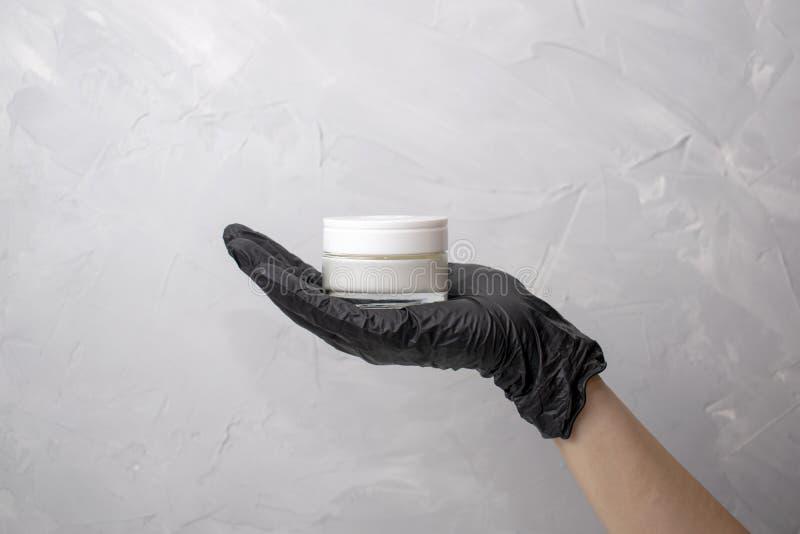 As mãos fêmeas na luva médica preta guardam o frasco com creme As mãos das mulheres com o frasco cosmético branco no fundo cinzen foto de stock royalty free