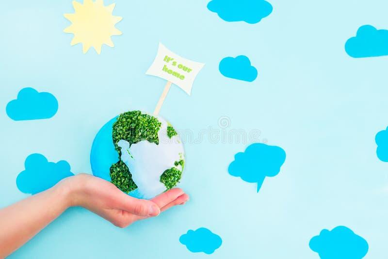 As mãos fêmeas que guardam o papel da terra e a colagem dos brotos do verde modelam com ela o ` s nosso ponteiro home no fundo az foto de stock