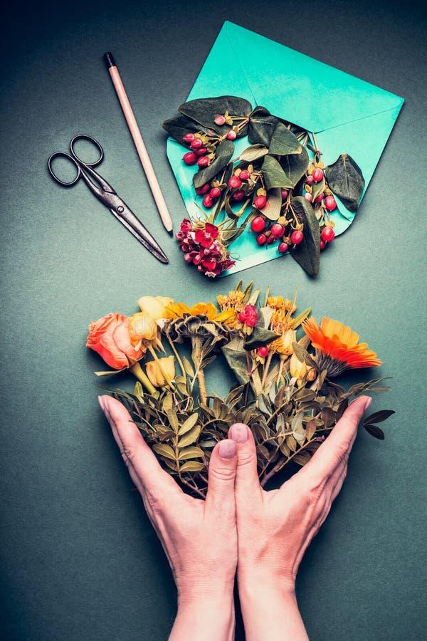 As mãos fêmeas que guardam um outono criativo florescem o ramalhete no florista o fundo da tabela que do espaço de trabalho com a imagens de stock