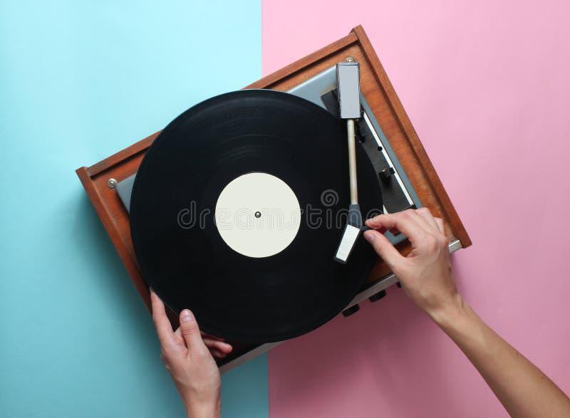 As mãos fêmeas usam o jogador retro do vinil em um fundo pastel cor-de-rosa azul DJ Vista superior foto de stock