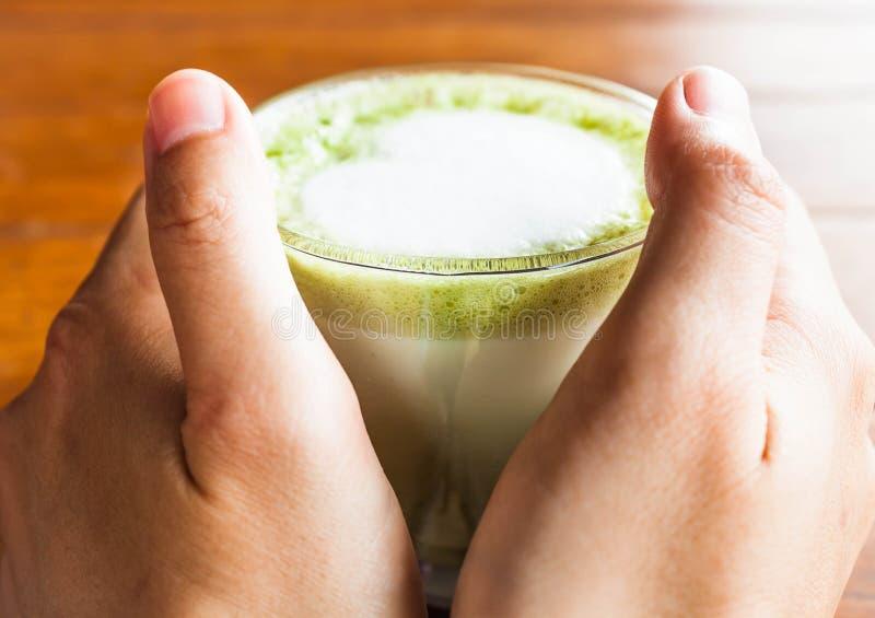 As mãos guardam a bebida quente do chá verde do matcha fotografia de stock