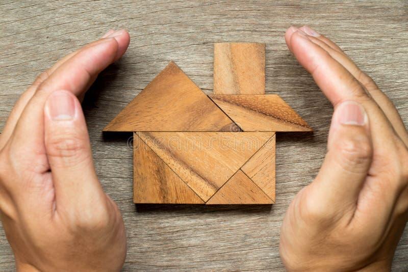 As mãos guardam o enigma do tangram na forma home fotos de stock royalty free