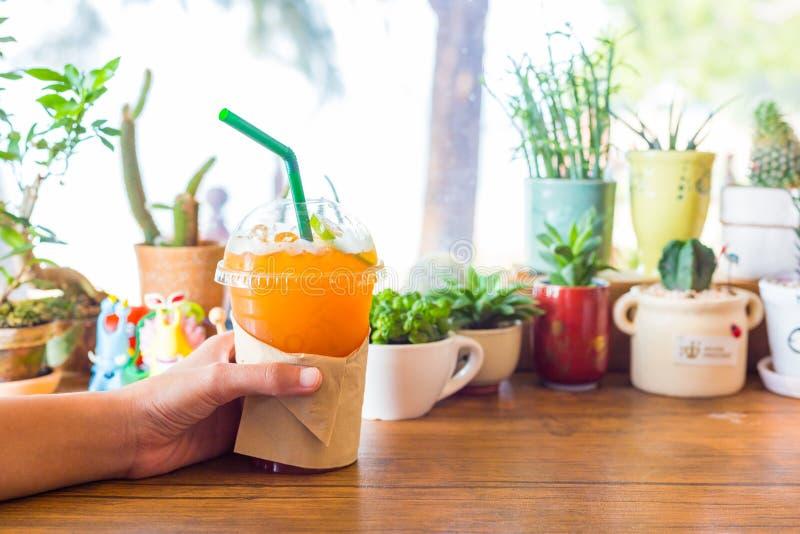 As mãos guardam o limão do chá de gelo na tabela de madeira na cafetaria fotografia de stock