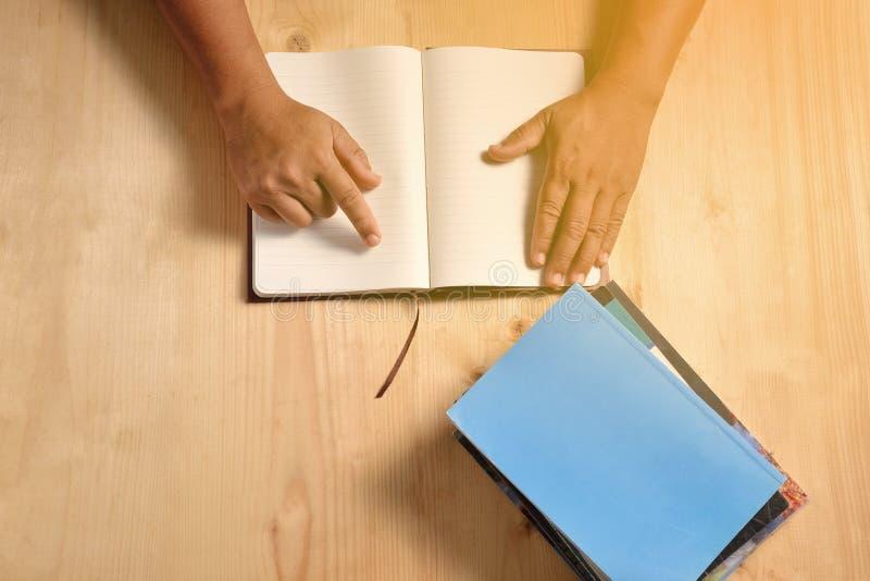 As mãos humanas abrem o caderno vazio imagens de stock