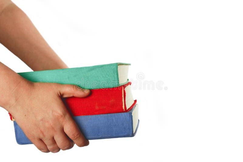 As mãos humanas que levam a pilha dos livros no branco isolaram o fundo imagens de stock royalty free
