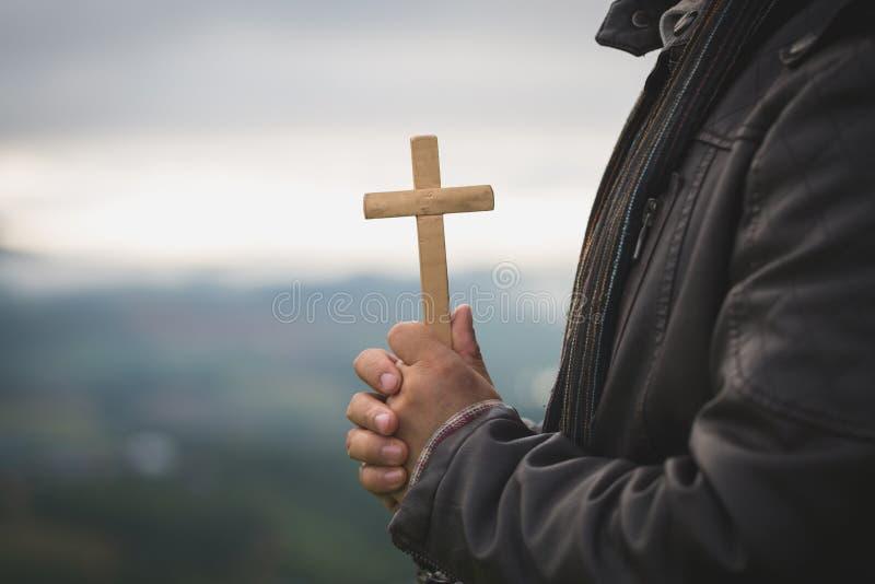 As mãos humanas que mantêm uma cruz santamente e rezaram para bênçãos do deus, conceito do deus da adoração do caso amoroso - Ima fotos de stock