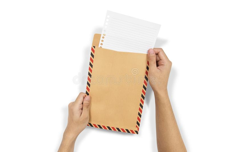As mãos introduzem o papel no envelope marrom foto de stock