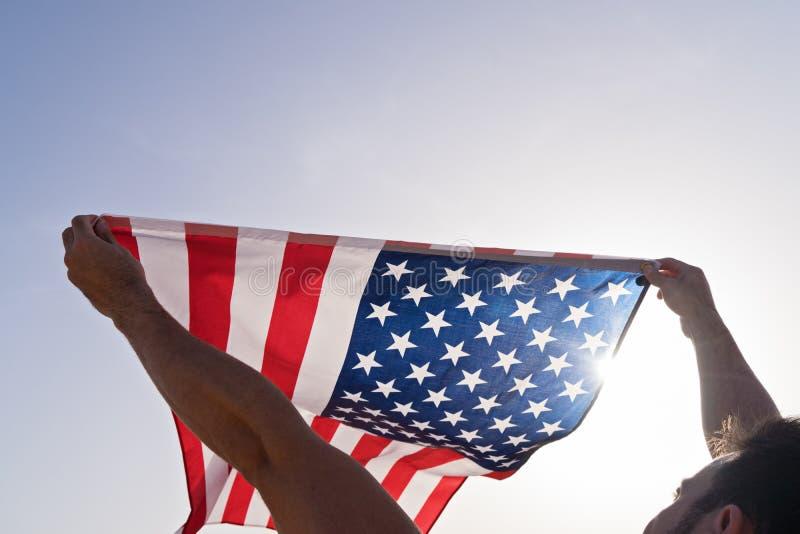 As mãos levantadas do homem com ondulação da bandeira americana contra o céu azul claro imagens de stock royalty free