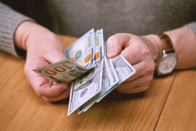 As mãos masculinas com relógio de pulso são consideradas dólares americanos foto de stock royalty free
