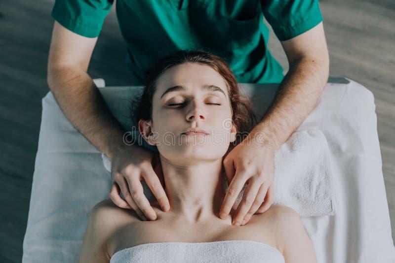 As mãos masculinas da massagem do massagista a cintura e o pescoço de ombro a uma jovem mulher fotos de stock