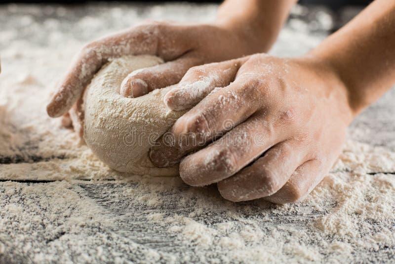 As mãos masculinas do cozinheiro chefe amassam a massa com farinha na mesa de cozinha fotografia de stock