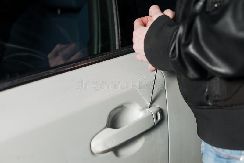 As mãos masculinas do ladrão abrem a porta de carro com chave de fenda foto de stock