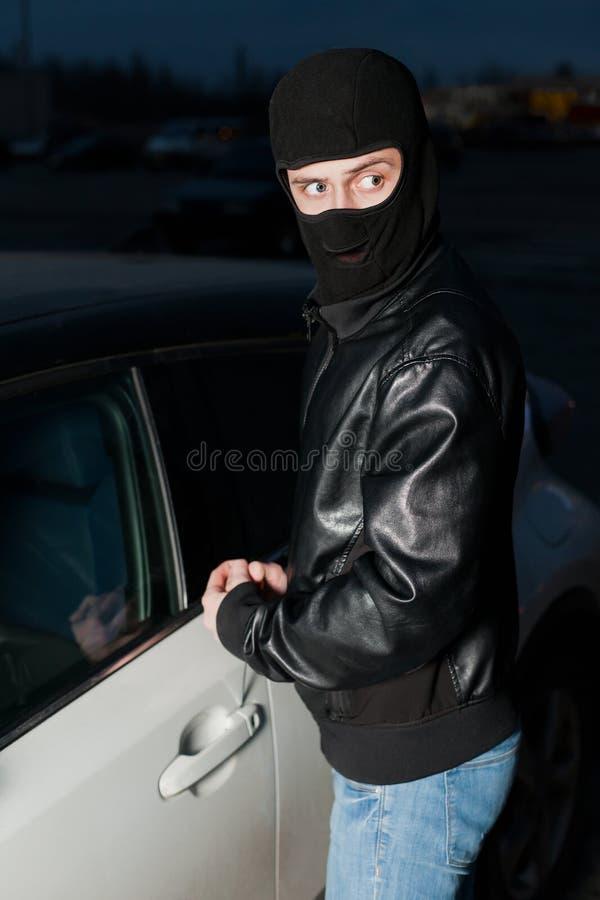 As mãos masculinas do ladrão abrem a porta de carro com chave de fenda imagens de stock royalty free