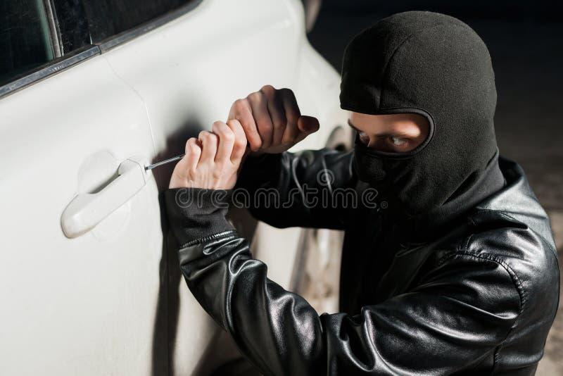 As mãos masculinas do ladrão abrem a porta de carro com chave de fenda fotos de stock royalty free