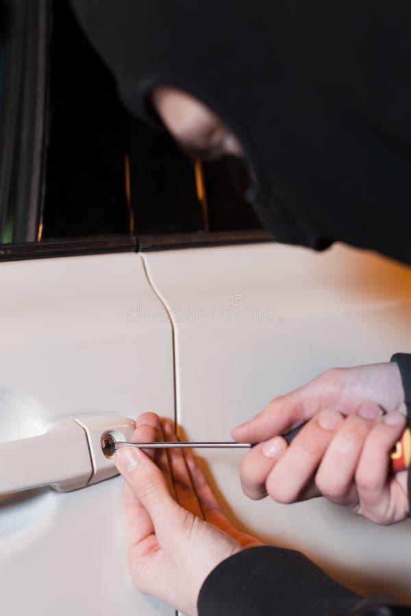 As mãos masculinas do ladrão abrem a porta de carro com chave de fenda fotografia de stock