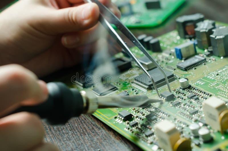 As mãos masculinas fecham-se acima de soldar um microchip Ferramentas fotografia de stock